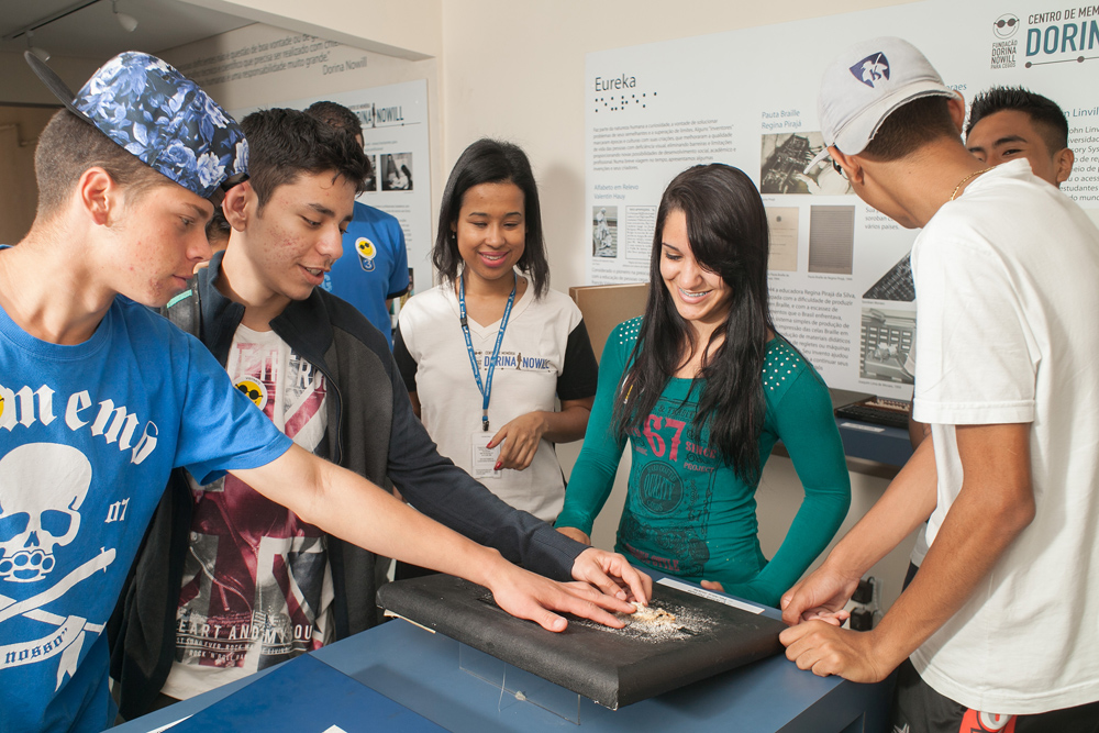 Descrição da imagem: foto de seis adolescentes e uma monitora da Fundação Dorina em volta de uma peça do Centro de Memória. Eles formam um semicírculo e três deles tateiam uma pintura em relevo ao centro. Fim da descrição.