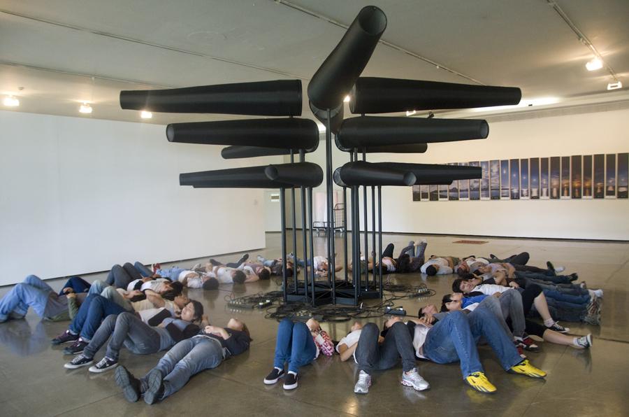 Descrição da imagem: Foto de cerca de 30 visitantes deitados no chão ao redor de uma obra no MAM. Eles formam um círculo em volta de uma estrutura metálica de cerca de 3 metros de altura com diversos tubos cônicos pretos. Fim da descrição.