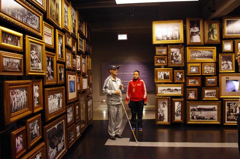 Descrição da imagem: foto de uma das salas do Museu do Futebol. A sala tem duas paredes repletas de fotografias antigas em preto e branco. No centro da imagem há um homem de bengala branca sobre um piso tátil e uma moça ao seu lado. Fim da descrição.