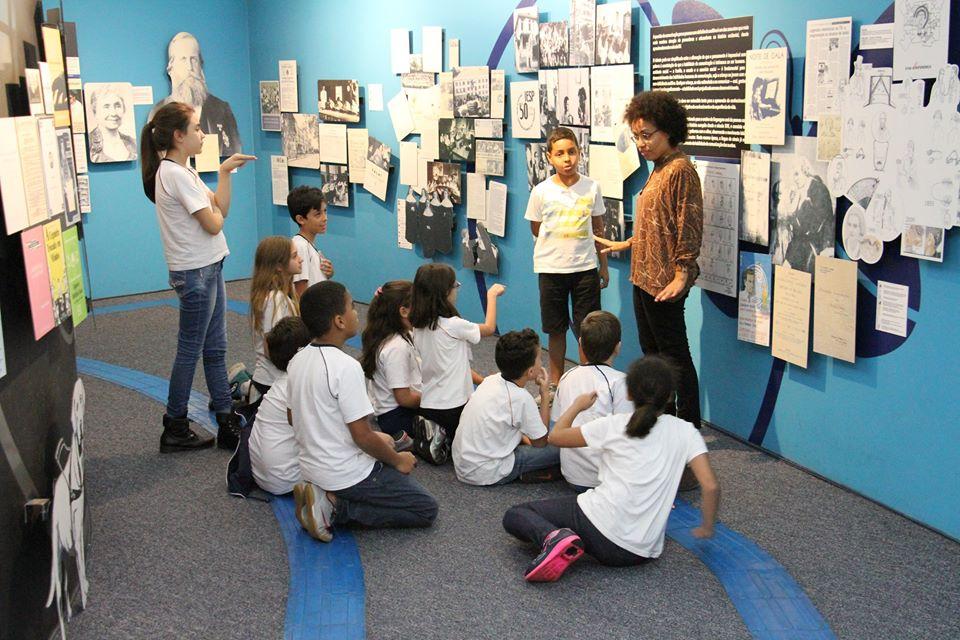 Descrição da Imagem: fotografia de um grupo de crianças em frente a um painel com diversos cartazes e figuras. A educadora está de costas para o painel. Fim da descrição.