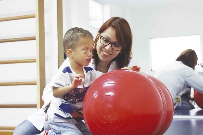 Descrição da imagem: foto de Nícolas fazendo um exercício com a fisioterapeuta Danielle. Ele está ajoelhado e de perfil, com a mão apoiada em uma grande bola vermelha de borracha. A fisioterapeuta está ao seu lado, abaixada, olhando pra ele e sorrindo. Fim da descrição.