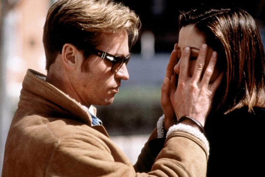 Descrição da imagem: cena do filme À primeira vista. Um homem de óculos escuros toca o rosto de uma moça com as duas mãos. Fim da descrição.