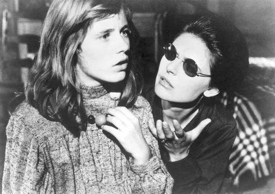 Descrição da imagem: cena em preto e branco do filme O Milagre de Anne Sullivan. Uma garota olha pra frente. Ao seu lado, uma mulher olha pra ela e gesticula com uma mão à frente do rosto. Ela usa óculos escuros. Fim da descrição.