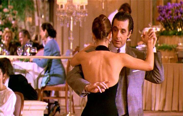 Descrição da imagem: cena do filme Perfume de Mulher. Um casal é retratado da cintura pra cima, dançando em um restaurante. Fim da descrição.
