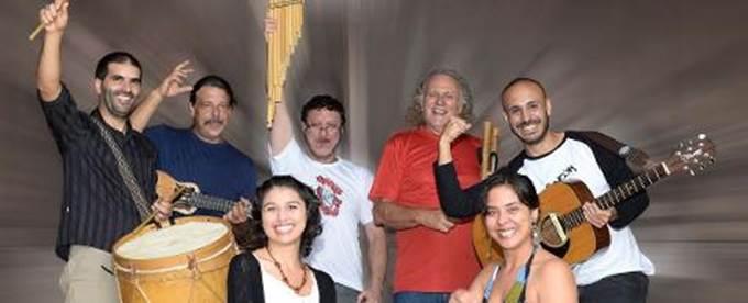 Descrição da imagem: Foto dos sete componentes do Grupo Tarancón: os cinco músicos estão em pé, segurando seus instrumentos e com um braço para cima. As duas cantoras estão abaixadas, em primeiro plano, à frente do grupo. Da esquerda para direita: Jonathan Andreoli (bombo leguero), Jorge Miranda (baixo), Ademar Farinha (flauta andina), Emílio de Angeles (flauta andina), Federico Caravatti (violão) e as cantoras: Natália Gularte e Maetê Gonçalves.