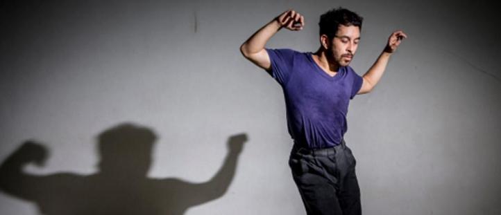 Descrição da imagem: foto do dançarino Eduardo Fukushima. Ele está retratado dos joelhos pra cima, com os braços levantados e olhos fechados. Fukushima usa camiseta roxa e calça preta. Ao fundo há a sombra do dançarino projetada numa parede branca. Fim da descrição.