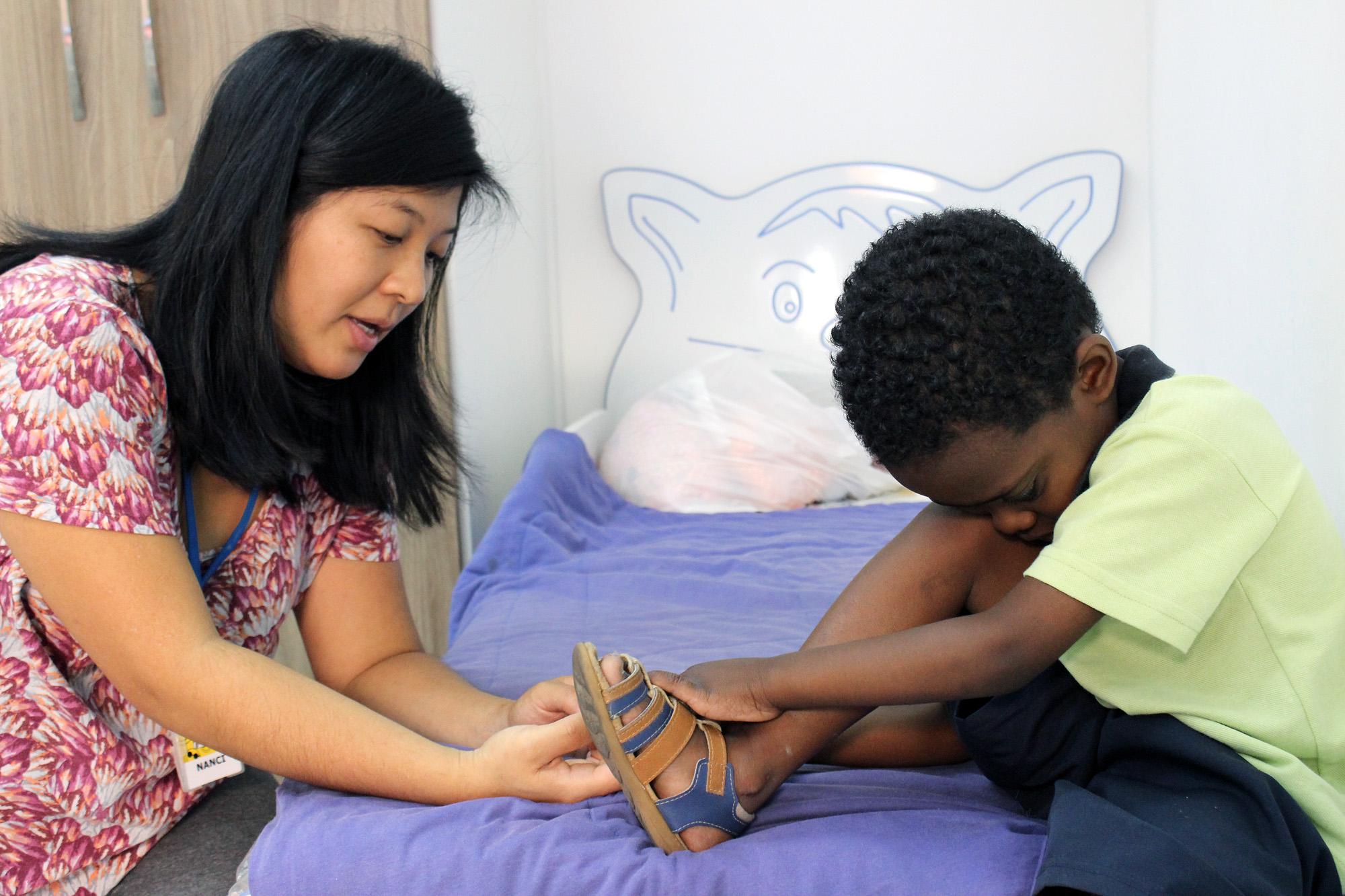 Descrição da imagem: foto de Cris abotoando sua sandália. Ele está sentado de perfil com o rosto encostado no joelho e o pé direito sobre a cama. Ao seu lado, à esquerda na foto, está a terapeuta Nanci Hara. Ela também está de perfil, orientando o menino. Fim da descrição.
