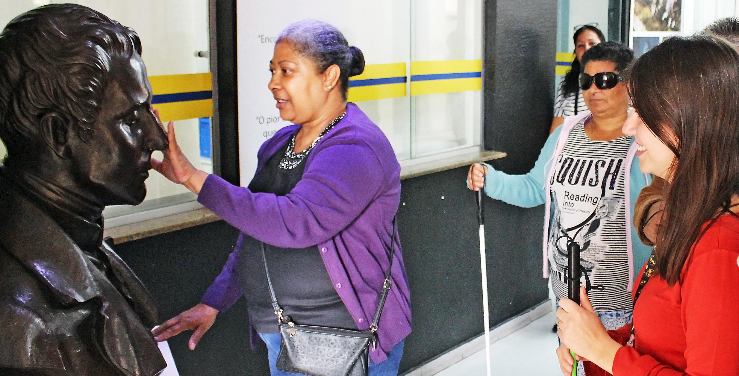 Descrição da imagem: foto de uma mulher tateando o busto de Louis Braille no Centro de Memória da Fundação Dorina. Ela está de perfil, olhando em direção à escultura. Atrás dela, à direita na foto, estão outras quatro pessoas. Fim da descrição.