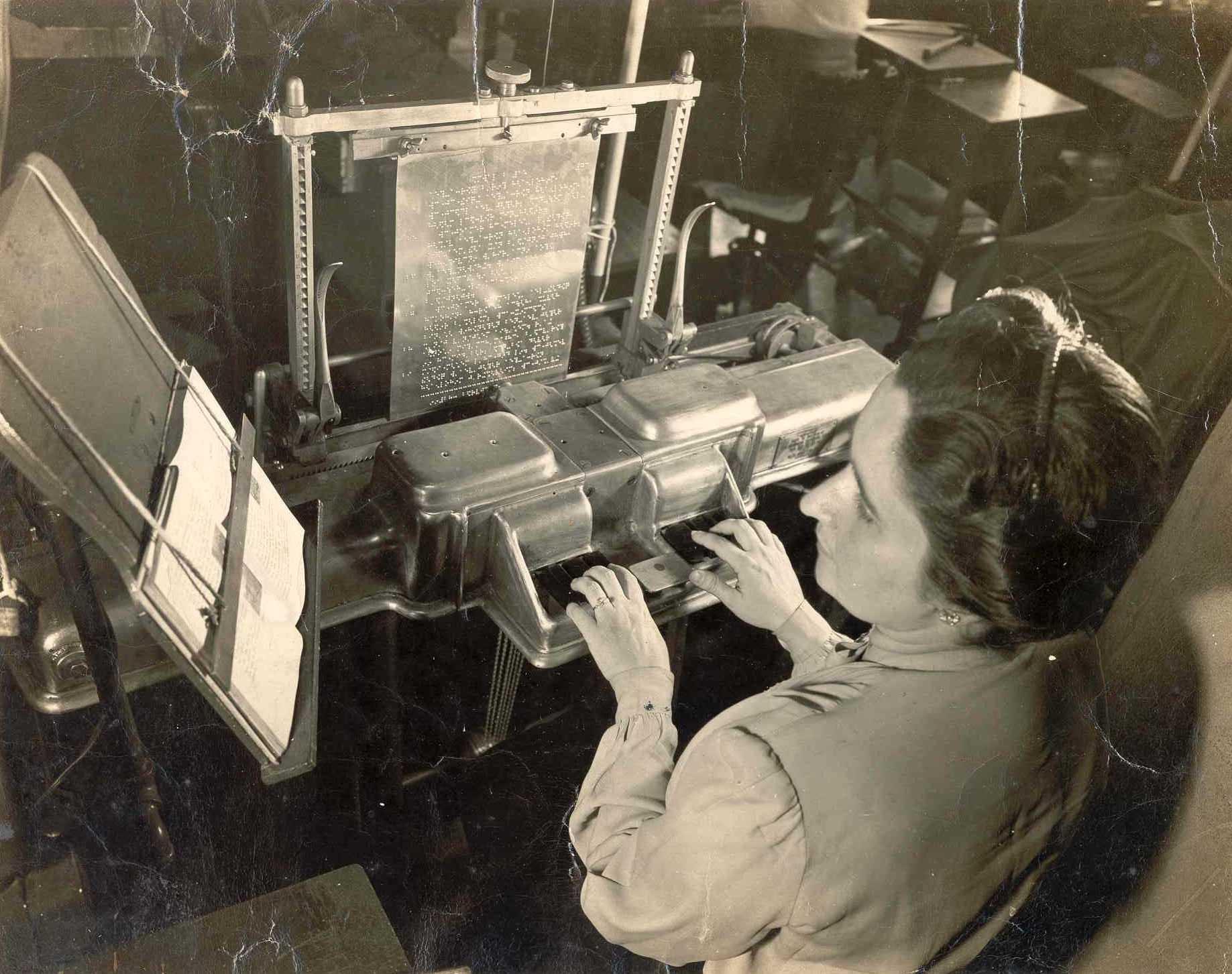 Foto em preto e branco de uma mulher fazendo a gravação de uma matriz braile para a produção de livros.