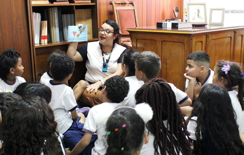 Foto de um grupo de crianças sentadas no chão junto com uma educadora da Fundação Dorina, que exibe um livro.