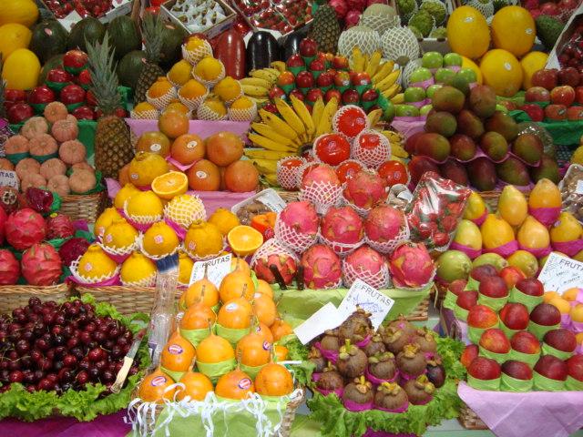 Descrição da imagem: foto de diversas frutas empilhadas em prateleiras de uma banca. Fim da descrição.