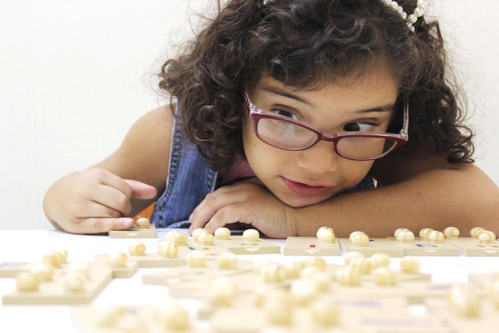 Descrição da imagem: foto de Ana Carolina, uma criança de 6 anos, manuseando peças de um alfabeto braile de madeira sobre uma mesa. Fim da descrição.