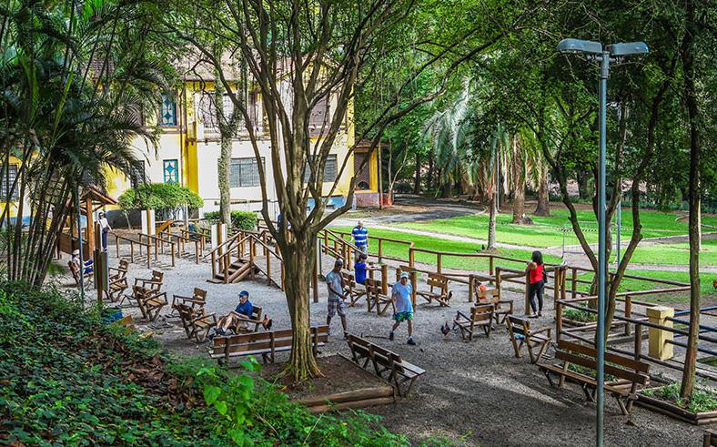 Descrição da imagem: foto do Parque da Água Branca. No centro há vários bancos e aparelhos de madeira com algumas pessoas circulando. Ao redor há inúmeras árvores. Fim da descrição.