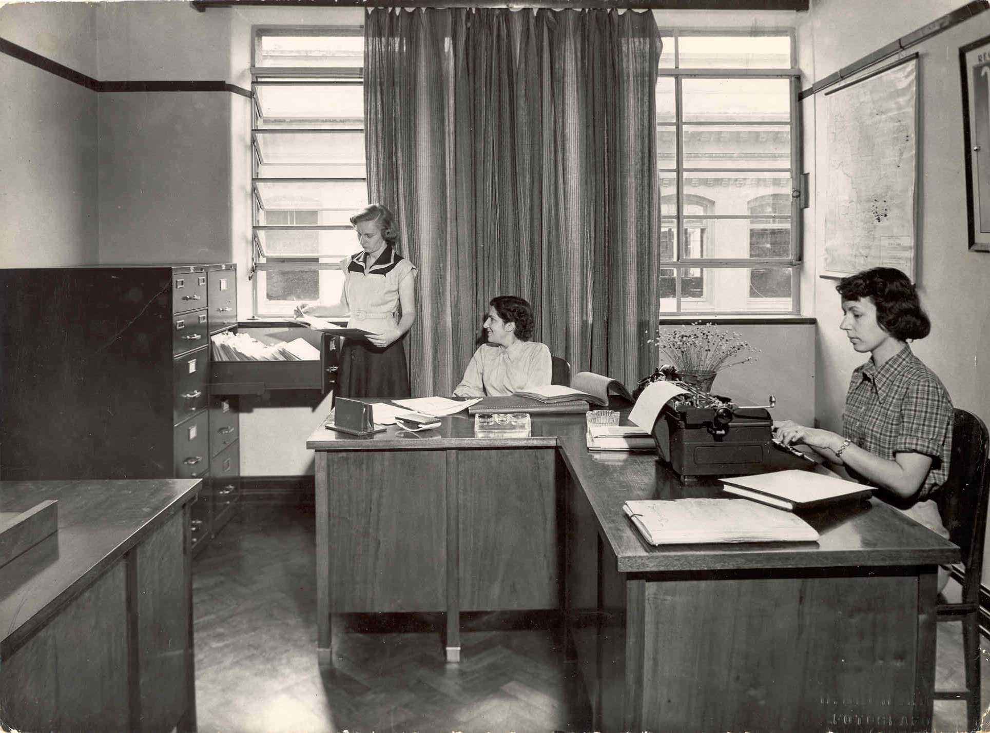 Imagem preto e branco. Três mulheres trabalhando na primeira sede da Fundação.