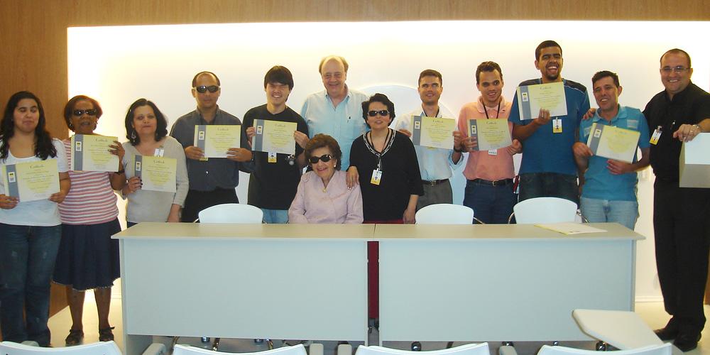 Descrição da imagem: Foto de Dorina Nowill e Regina Oliveira com um grupo de formandos do curso de revisão em braile. Elas estão ao centro. Todos estão perfilados, olhando pra frente e sorrindo. Os alunos exibem o diploma. Fim da descrição.
