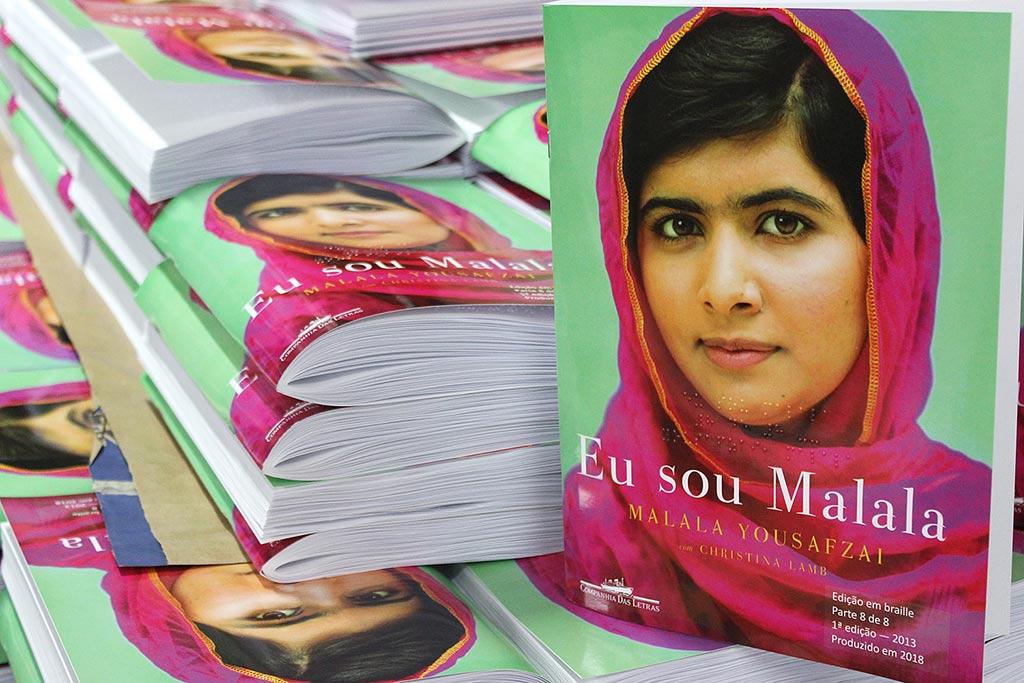 """Descrição da imagem: foto do livro """"Eu sou Malala"""" em uma pilha de outros exemplares do mesmo título. A capa traz a foto de Malala sorrindo  e usando um lenço rosa sobre fundo verde."""