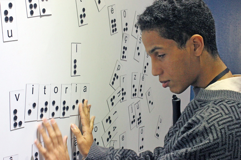 """Descrição da imagem: foto de Lucas tocando um painel magnético com diversas letras em braille. Ele está de perfil, com as duas mãos sobre a palavra """"vitória"""" afixada no painel."""
