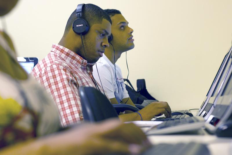 Descrição da imagem: foto de dois rapazes de aproximadamente 22 anos à frente de computadores. Eles estão de perfil e usam fones de ouvido. Na parte inferior da imagem é possível ver a mão de uma terceira pessoa sobre o teclado, na mesma mesa de trabalho.
