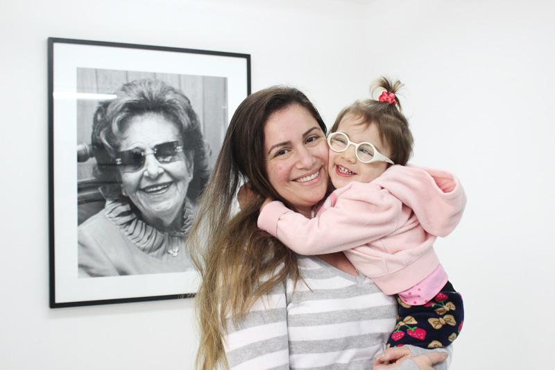 Descrição da imagem: foto de Nadia com Lívia no colo. A menina dá um abraço apertado na mãe. As duas olham pra frente e sorriem. Ao fundo há um retrato em preto e branco de Dorina Nowill na parede.