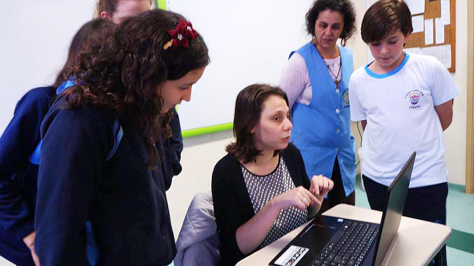 Descrição da imagem: foto de Isabela sentada em uma mesa escolar com um notebook à sua frente. Ao redor, de pé, estão três meninas, um menino e uma mulher de avental azul, olhando para o notebook.