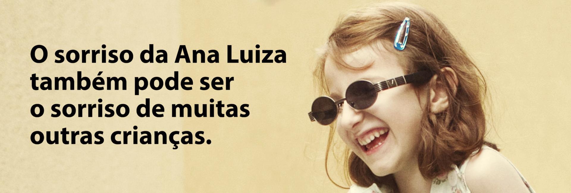 """Descrição da imagem: foto uma menina de 6 anos atendida pela Fundação Dorina. Ela é retratada de perfil, do ombro pra cima, usa óculos escuros e exibe um largo sorriso! À esquerda, a frase """"O sorriso da Ana Luiza também pode ser o sorriso de muitas outras crianças"""""""