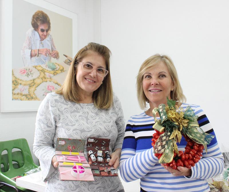 Descrição da imagem: foto de Marize e Gel Dellamana, duas voluntárias do Bazar da Costura. Elas estão sorrindo, olhando pra frente e exibindo uma guirlanda, uma caixinha de costura e um kit de manicure. Na parede ao fundo há uma fotografia de Dorina Nowill tricotando uma toalha.