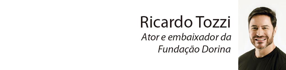 Descrição da imagem: retrato de Ricardo Tozzi do peito pra cima. Ele tem pele clara, cabelos castanhos, curtos e lisos, barba curta, usa camiseta preta, olha pra frente e sorri.