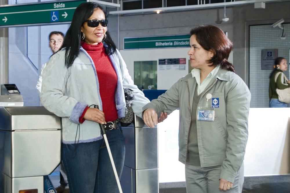 Descrição da imagem: foto de uma mulher de óculos escuros e bengala passando por uma catraca segurando o braço de uma funcionária do metrô.