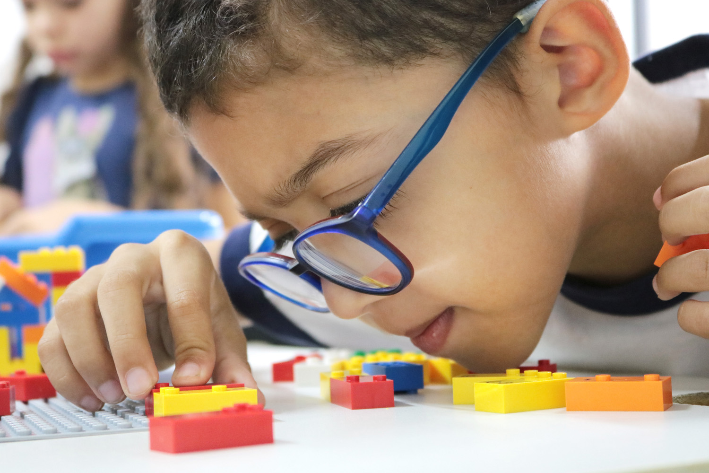 Descrição da imagem: foto de um garoto manuseando peças do LEGO Braille Bricks. Ele está de perfil, usa óculos e tem o rosto bem próximo às peças, com o queixo sobre a mesa.