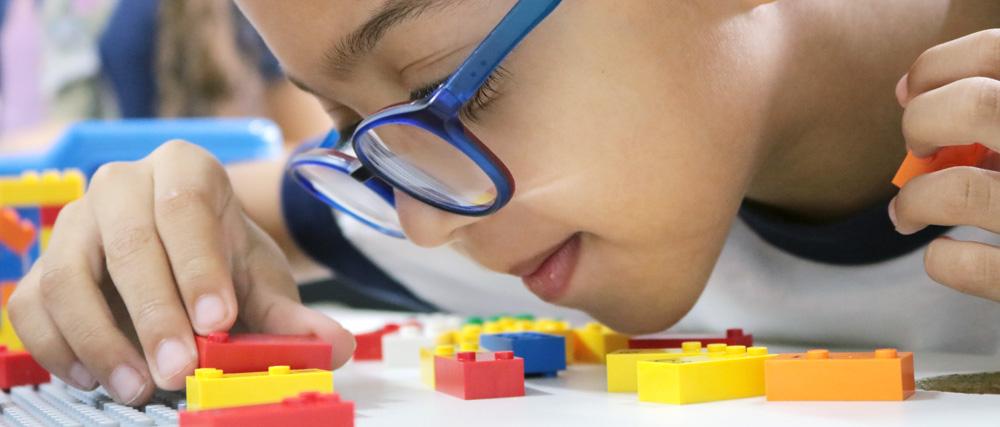 Descrição da imagem: foto de um menino de óculos manuseando pequenos blocos coloridos de montar. Ele tem o rosto bem próximo à mesa.