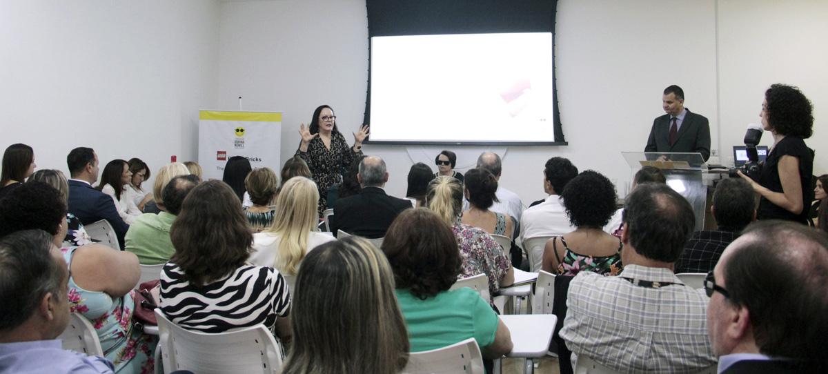Descrição da imagem: foto do auditório da Fundação Dorina com dezenas de pessoas sentadas. À frente delas, Ika Fleury gesticula com as duas mãos abertas. Ao fundo, um telão.