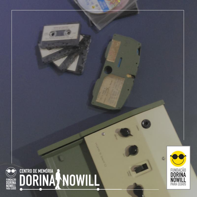 Foto de um toca fita em cima de um fundo roxo, na parte de baixo estão os logos da fundação Dorina e do Centro de Memória