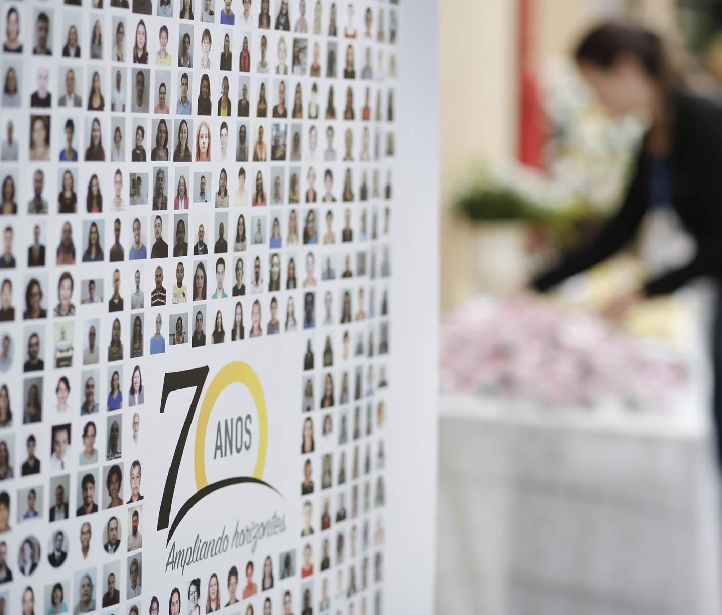 Descrição de imagem: fotografia colorida em que é possível ver um painel com várias fotos de rostos de pessoas e ao centro o logo dos 70 anos da Fundação Dorina. Ao fundo, bem desfocada, a silhueta de uma mulher. Fim da descrição.