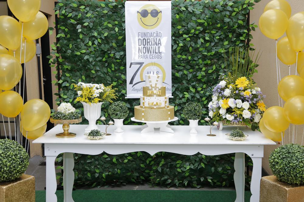 Descrição de imagem: Fotografia colorida de mesa da festa em comemoração aos 70 anos. Há um bolo de três andares, branco e dourado, cercado por vasos com folhas e flores brancas e amarelas. Fim da descrição.