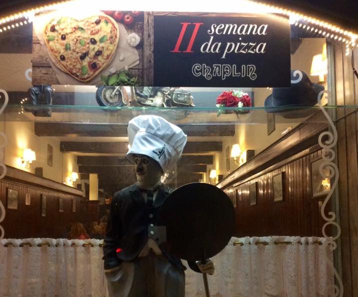 Fotografia de uma fachada de restaurante. No topo, um banner com a imagem de uma pizza em formato de coração e o texto II Semana da Pizza Chaplin. Abaixo um boneco de Charlie Chaplin com chapéu de pizzaiolo