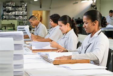Foto de pessoas perfiladas trabalhando na produção de livros em Braille.