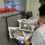 Foto de duas curadoras do centro de memória, organizando os arquivos de fotos antigas da fundação.