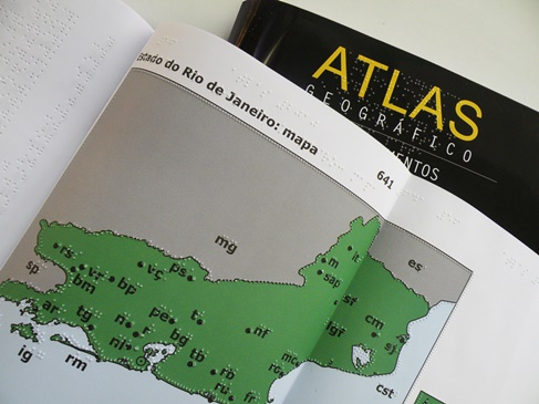 Imagem em destaque: foto de um atlas em braille. Fim da descrição.