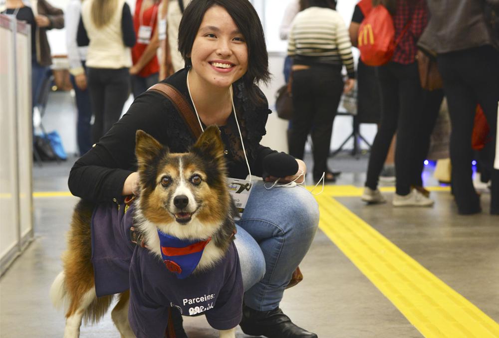 Descrição da imagem: foto colorida de Marina Yonashiro, da Fundação Dorina, abaixada ao lado de um cão terapêutico, da raça Corgi. Marina tem traços orientais e cabelos curtos, olha pra frente e sorri. Fim da descrição.