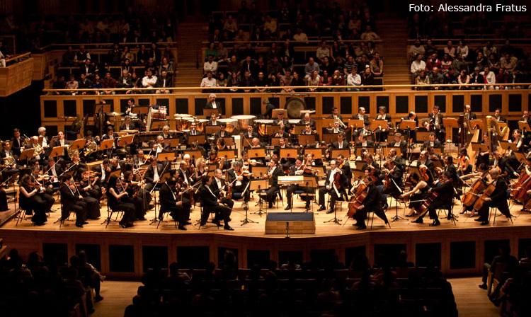 Descrição da imagem: foto da Orquestra Sinfônica do Estado de São Paulo. Dezenas de músicos estão tocando em um palco de madeira. Eles usam ternos pretos. Ao fundo, em segundo plano, está a plateia, com dezenas de pessoas sentadas. Fim da descrição.