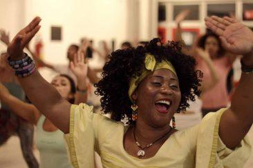 Descrição da imagem: foto de uma mulher dançando. Ela é retratada do peito pra cima, sorrindo, com os braços levantados e as palmas das mãos voltadas pra cima. A mulher é negra, usa um colar de concha, brincos, pulseiras, um lenço amarelo no cabelo e uma bata amarela. Ao fundo há diversas outras pessoas fazendo o mesmo movimento. Fim da descrição.