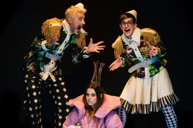 Foto de três atores interpretando uma peça infantil com figurino medieval.
