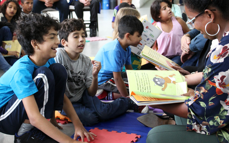 foto de pessoas lendo livros da coleção regionais para crianças, todos sentados ao chão.