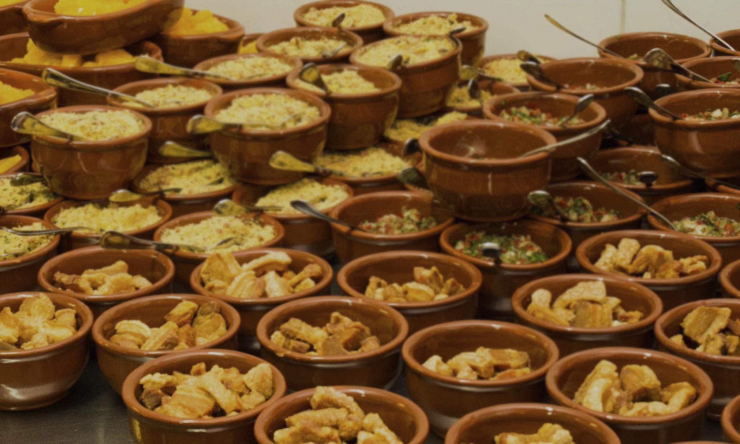 Foto de várias cumbucas com farofa, vinagrete e torresmo