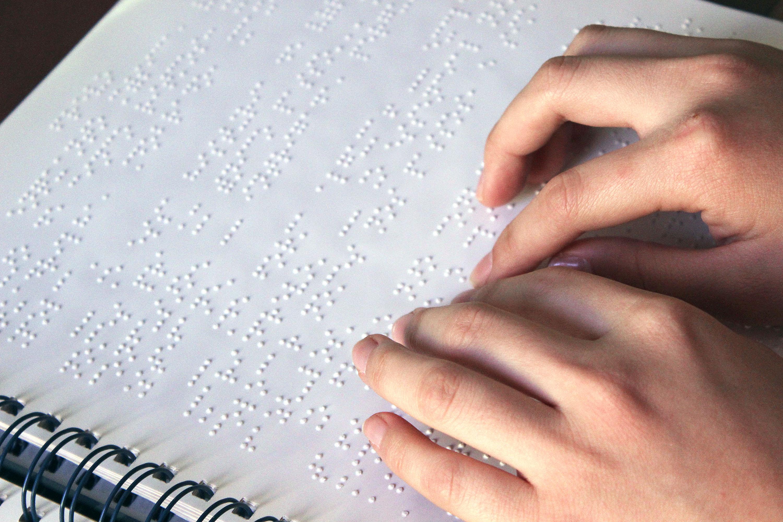 Descrição da imagem: foto de duas mãos tateando um texto em braille em uma folha branca. Fim da descrição.