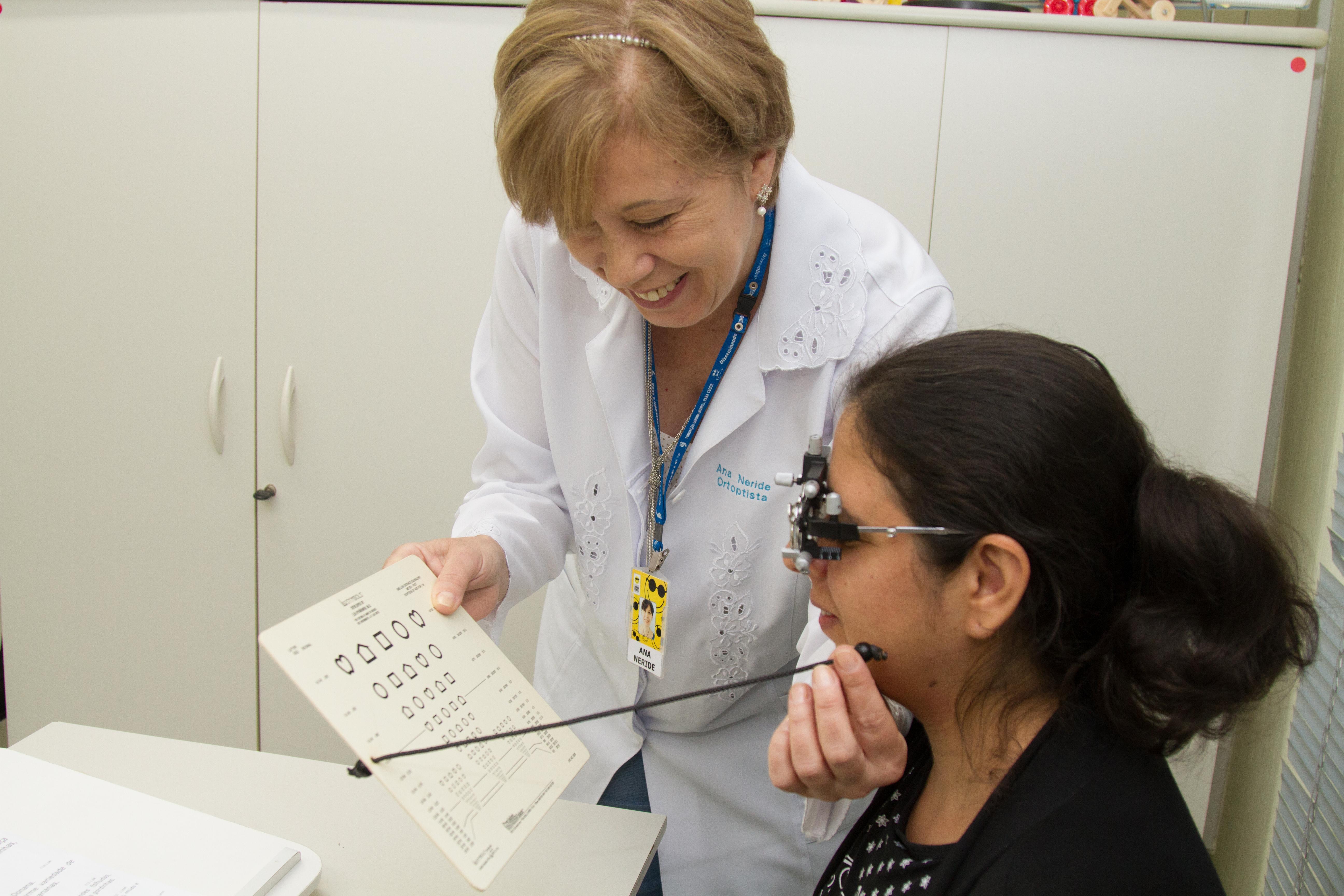 Descrição da imagem: moça sendo atendida em consulta oftalmológica por uma profissional da Fundação Dorina Nowill para Cegos. Fim da descrição.