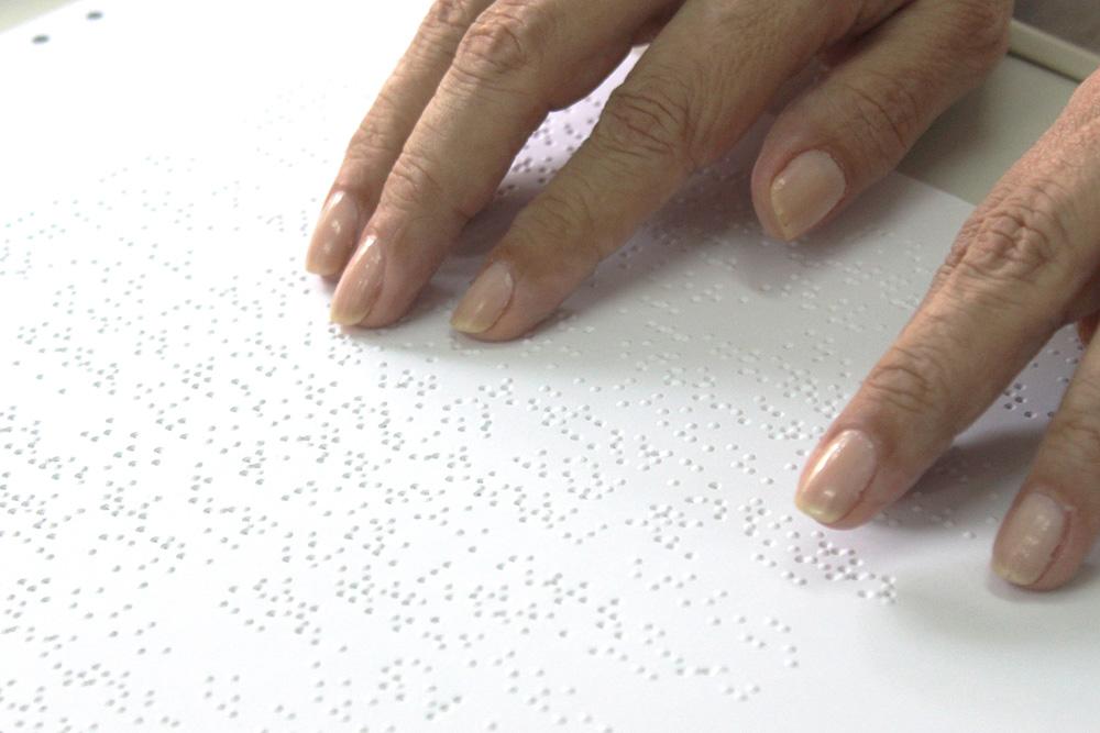 Descrição da imagem: foto de duas mãos tateando uma página em braile. Fim da descrição.