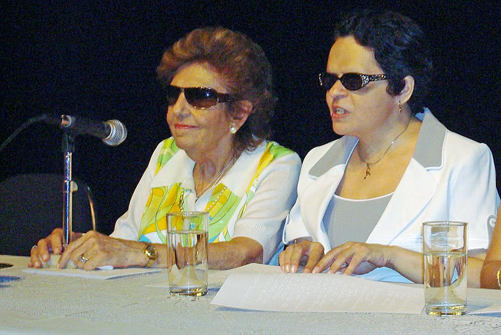 Foto de Dorina Nowill e Regina Oliveira. Elas estão sentadas com as mãos sobre a mesa, que tem um microfone e dois copos d'água. Regina está tateando um texto em braile. Ambas usam óculos escuros.