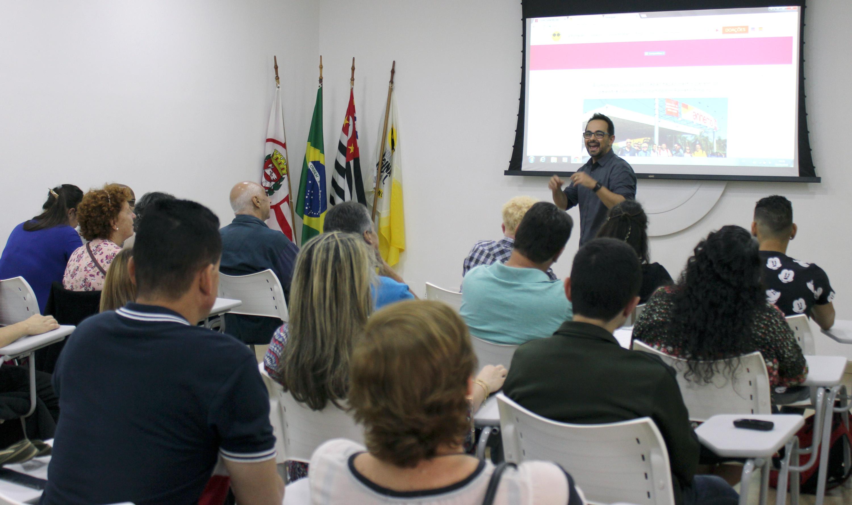 Descrição da imagem: foto de Renato Ribeiro falando para cerca de 30 pessoas no auditório da Fundação Dorina. Ele é moreno, tem cabelos curtos, veste camisa cinza, usa óculos e relógio preto. Atrás dele há um telão.