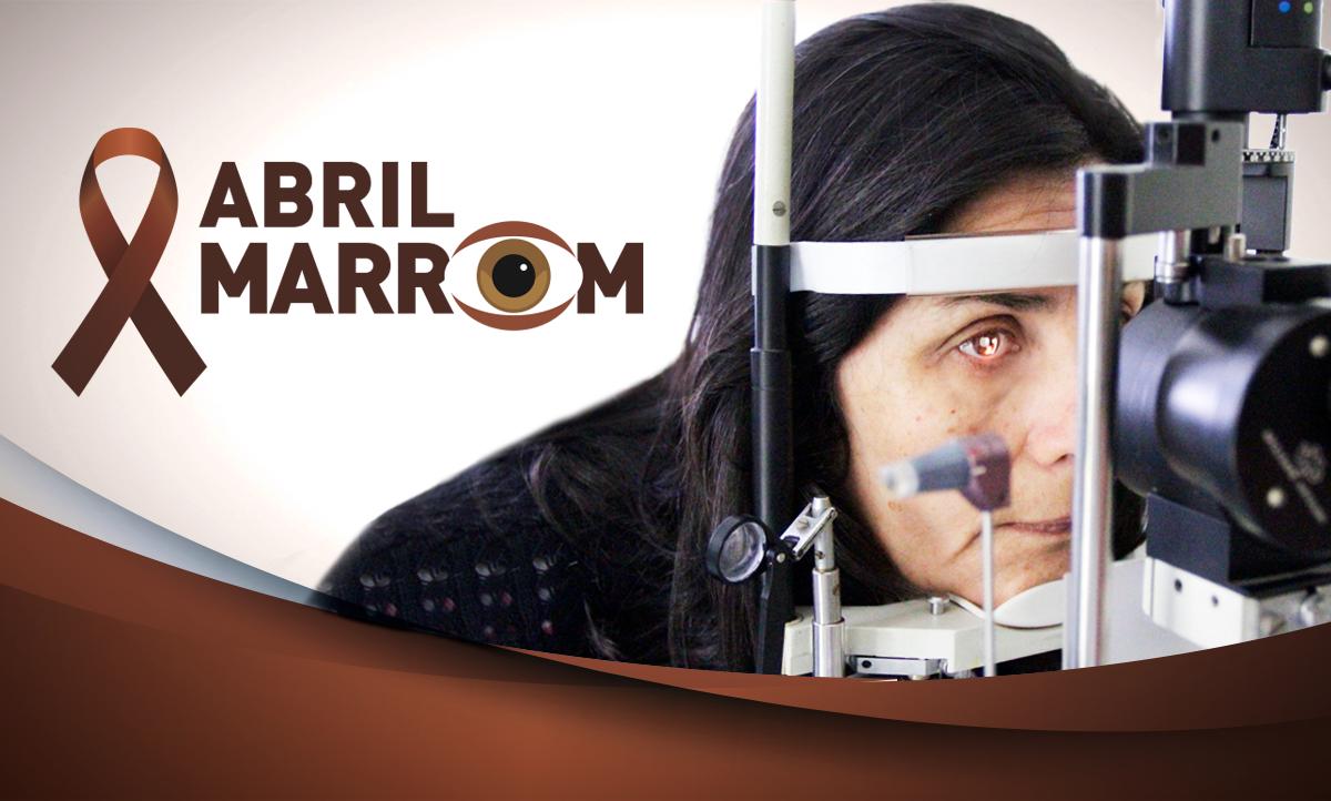"""Descrição da imagem: foto de uma mulher realizando exame de vista. Ela está com o rosto apoiado em um aparelho que emite uma luz alaranjada em seu olho. Ao lado esquerdo da foto há o título """"Abril Marrom""""."""